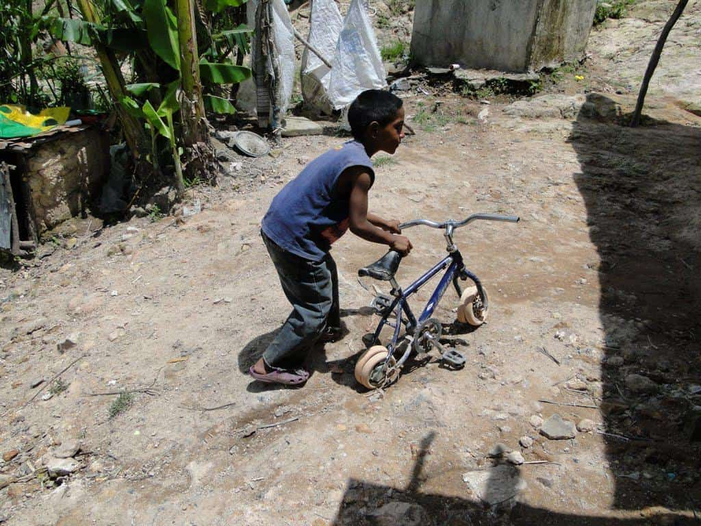 boy in poverty with bike