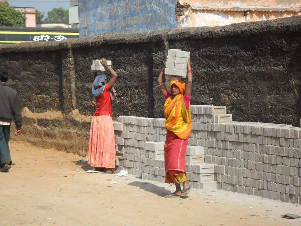 women carrying bricks